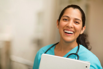 Happy Hispanic medial provider at work stock photo.