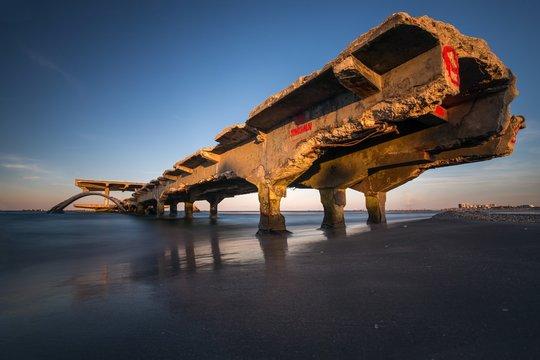 Old broken bridge over the sea under a clear blue sky