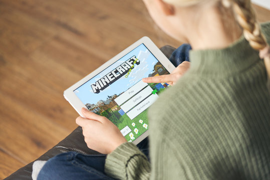 January 5, 2020, Kaliningrad, Russia. Little girl with blond hair start playing Minecraft game on Apple iPad Air. The problem of gambling addiction in children and adolescents