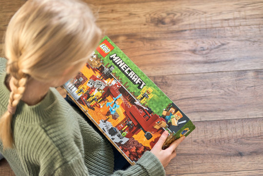 January 5, 2020, Kaliningrad, Russia. A little girl with blond hair is holding a new box of Lego Minecraft and looks at it.