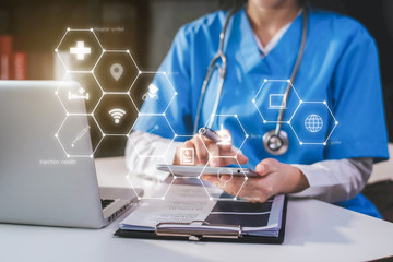 Doctor working on laptop computer and tablet and medical stethoscope on clipboard on desk, electronics medical record system EMRs concept.