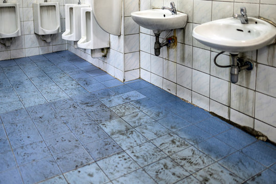 Old scruffy toilet where the floor is wet and filled with dirty footprints of student,filthy of urinals,washbasin,tiled wall, unhygienic,dirty restroom or has not cleaned the bathroom,back to school