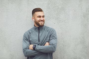 Bearded guy in sportswear on gray background.