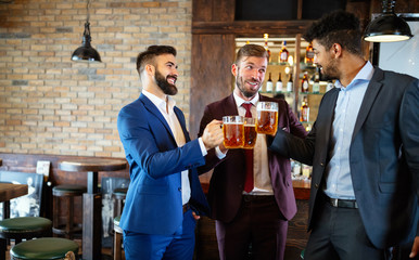 Foto auf Leinwand Alkohol Happy young businessmen drinking beer and talking at pub after work