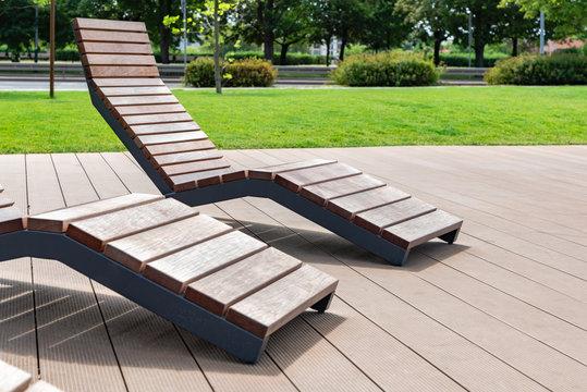 Modern city architecture design concept - empty wooden sun beds in the public park
