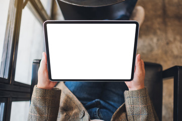 Top view mockup image of a woman holding black tablet pc with blank white screen