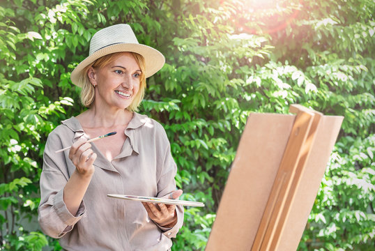 Portrait of happy senior caucasian artist mature woman paint with water color outdoor greenery class. Old creative gifted artist home school education. Healthy activity hobby lifestyle.