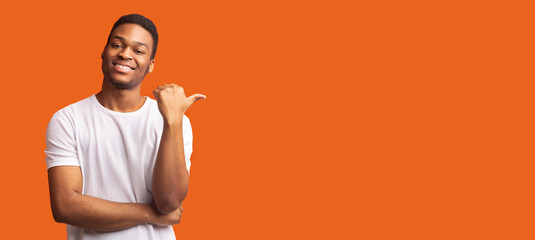 Fototapeta Young afro guy pointing at copy space with thumb up obraz
