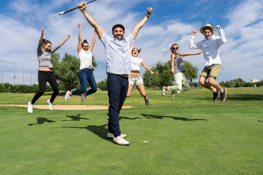 Man with his arms raised in a victorious expression with a group of people who are celebrating and jumping on a golf course