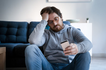 Portrait of worried guy holding cellphone at home