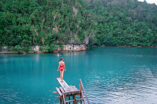 Vacation and activity. Young woman in swimsuit enjoying blue tropical lagoon view standing on wooden springboard. Siargao Island, Philippines.