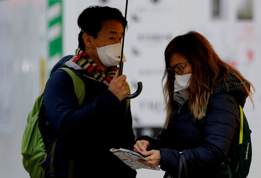Tourists from Australia check a map at a shopping district in Tokyo
