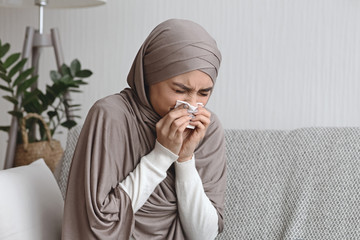 Sick muslim woman blowing runny nose to napkin at home