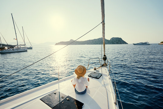 Luxury travel on the yacht. Young happy woman on boat deck sailing the sea. Yachting in Greece.
