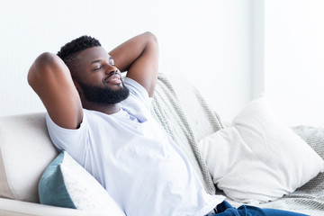 Relaxed african american man resting at home on sofa Wall mural