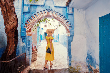 Foto op Aluminium Marokko Colorful traveling by Morocco. Young woman in yellow dress walking in medina of blue city Chefchaouen.