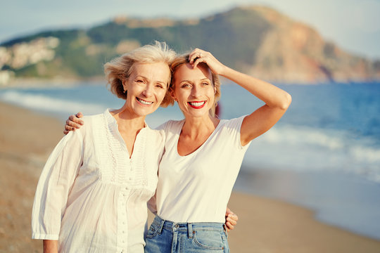 Outdoor portrait of smiling happy caucasian senior mother with her adult daughter hugging and looking at the camera on sea beach.