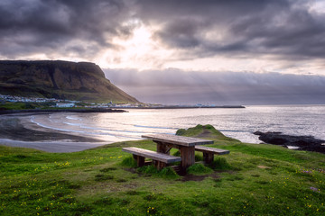 Amazing nature landscape with wooden table and bench, best place for rest and enjoy the views of the Atlantic coast of Iceland. Outdoor travel background