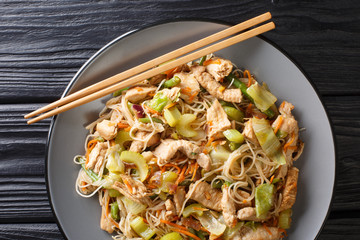 stir fried rice noodles pancit bihon with vegetables and meat close-up in a plate. Horizontal top...
