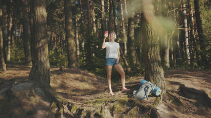 Woman with backpack use smartphone stand take picture look around in the fall forest on sunny summer day tourism nature mountain cellphone enjoy mobile landscape vacation happy outdoor slow motion