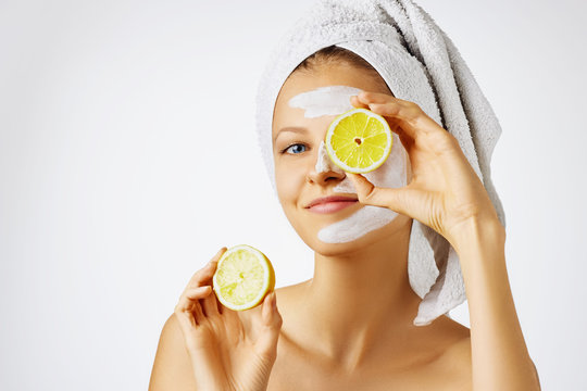 Cosmetology, skin care, face treatment, spa and natural beauty concept. Woman with facial mask holds lemons.