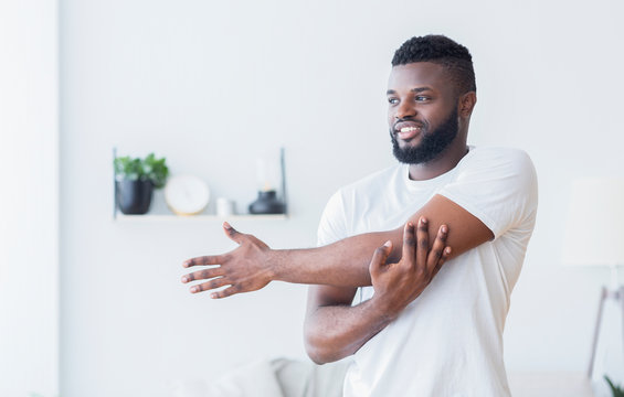 Young black man training and stretching arm at home