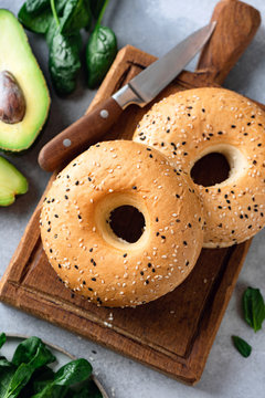 Sesame bagels on wooden board top view