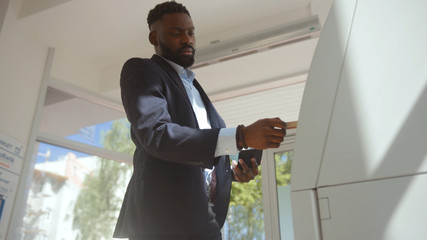 Afro-american man in suit trying to get money from an ATM machine. Automated teller machine failure with client at daytime in a bank.