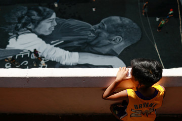 A fan of Kobe Bryant looks at a mural, painted in memory of him and his daughter Gianna hours after they died in a helicopter crash, on the basketball court of a housing tenement in Taguig City, Metro Manila