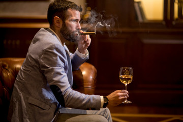 Young man tasting white wine and smoking cigar