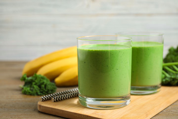 Tasty fresh kale smoothie on wooden table, closeup