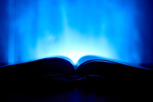 An open book with a glow in the background.