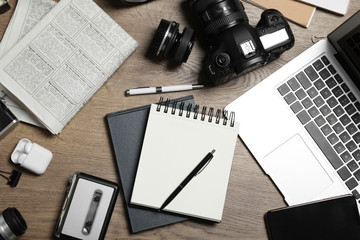 Flat lay composition with equipment for journalist on wooden table