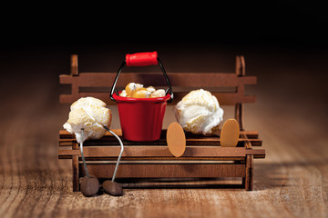 Funny scene with popcorn figures on a wooden table, sitting on a bench