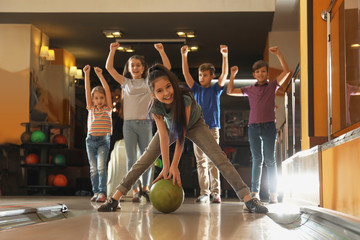 Girl throwing ball and spending time with friends in bowling club