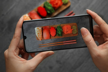 Blogger taking photo of sushi set at grey table, closeup
