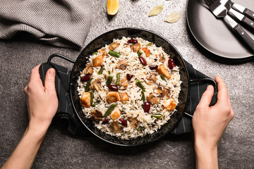 Woman with delicious rice pilaf at grey table, top view