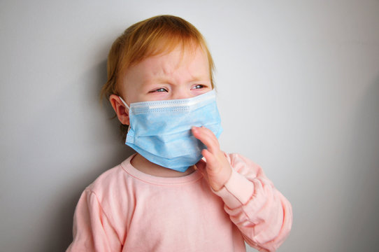 one healthy little baby crying. Medical mask on the baby. protect the child from diseases. stop the spread of the virus. wear a surgical mask.