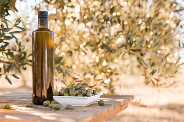green olives and oil on table in olive grove