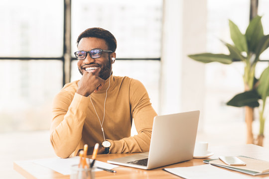 Happy black businessman in glasses listening to music