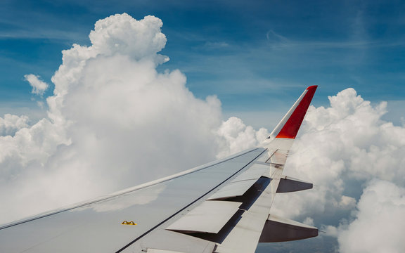 Flying and traveling. View of window at flying airplane, Plane wing on blue sky