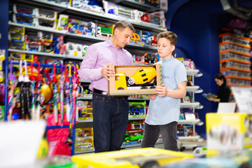 Teen boy with father visiting children toy store in search of big plastic car for gift