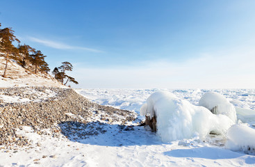 Icy and snowy shore of Baikal Lake on a frosty winter day. Ice hummocks cover the surface of the lake. Beautiful winter landscape. Natural background