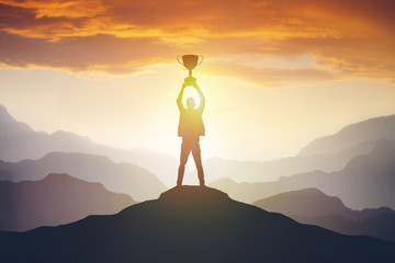 Silhouette of a man holding a trophy at sunset Fotobehang