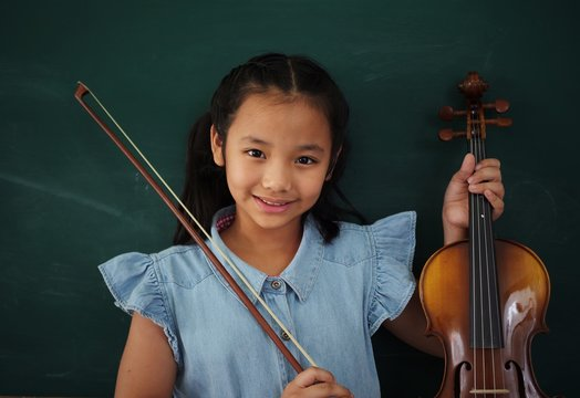 Portrait Of Smiling Girl Holding Violin Against Wall