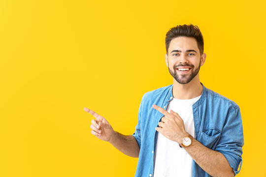 Handsome young man pointing at something on color background