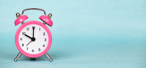 Save time, daylight saving concept, pink alarm clock on a blue background, web banner with copy space