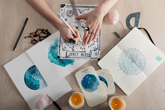 Top view of astrologer drawing birth chart by candles, crystals and watercolor paintings on cards on table