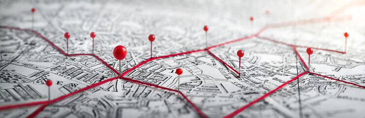 Spoed Fotobehang Macrofotografie Routes with red pins on a city map. Concept on the adventure, discovery, navigation, communication, logistics, geography, transport and travel topics.