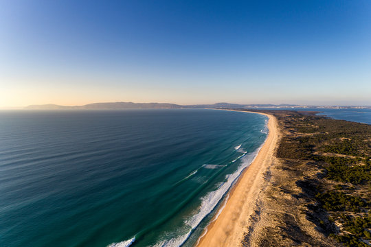 Aerial view of the Comporta Beach and the Troia Peninsula with the Arrabida Mountain on the background, in Portugal.